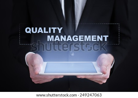 Businessman holding a tablet with qulity  management business concept. solution. - stock photo
