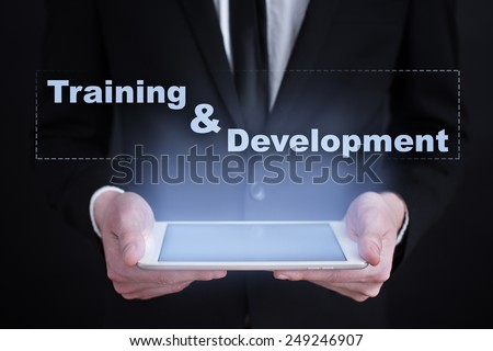 Businessman holding a tablet with time educationt concept.  training and development. - stock photo