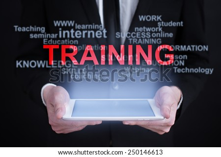 Businessman holding a tablet with training words cloud on the screen. business and education  concept. - stock photo