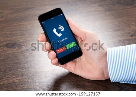 businessman holding a touch phone with blue screen and the phone ringing tube over the villages table - stock photo