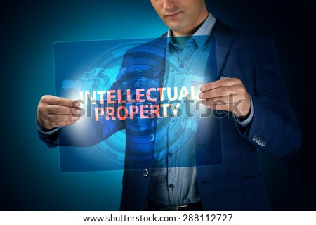 Businessman holding a transparent screen with an inscription a intellectual property. Business, technology, internet and networking concept. - stock photo