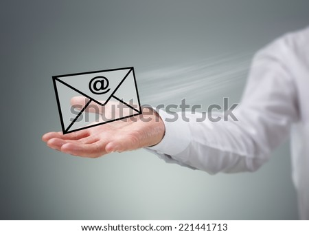 Businessman holding a virtual envelope with at symbol concept for e-mail, global communications, mail or contact us - stock photo