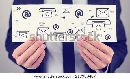 Businessman holding a white card or sign with a variety of different contact icons for mail, email, web and telephone in a communication concept. - stock photo