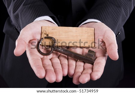 Businessman holding an old key (put your text on the wooden keychain) - stock photo