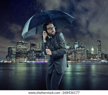 Businessman holding an umbrella - stock photo