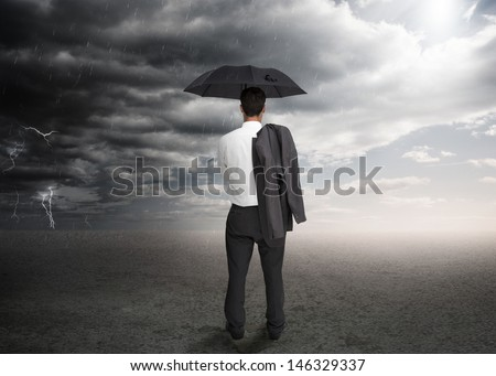 Businessman holding an umbrella and a jacket over his shoulder facing a storm - stock photo