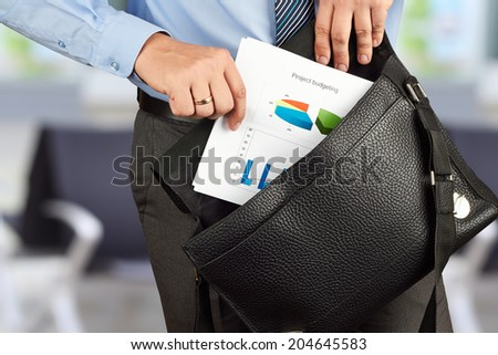 Businessman holding and getting out   documents with graphs  from his   leather briefcase.  - stock photo