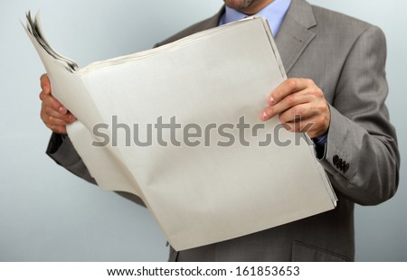 Businessman holding and reading a blank newspaper with copy space - stock photo