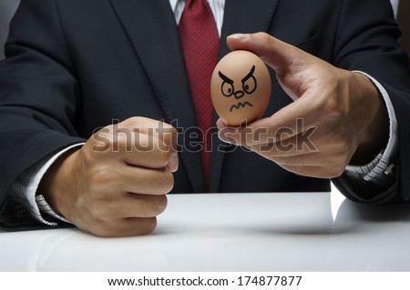 Businessman holding Angry Egg character and other hand fist hit the table - stock photo