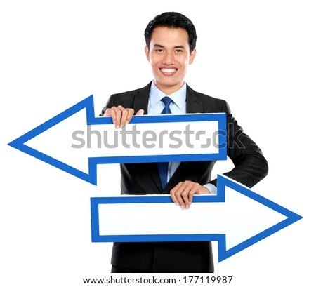Businessman holding arrow pointing right and left in hand on white background - stock photo