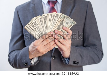 Businessman holding bank notes in white isolated background - stock photo