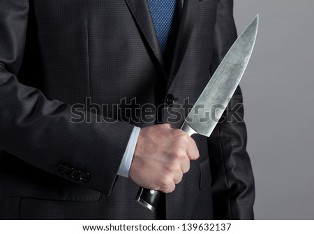 Businessman holding big knife in his hand - stock photo