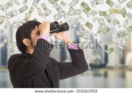 Businessman holding binoculars for search and check glowing business  - stock photo