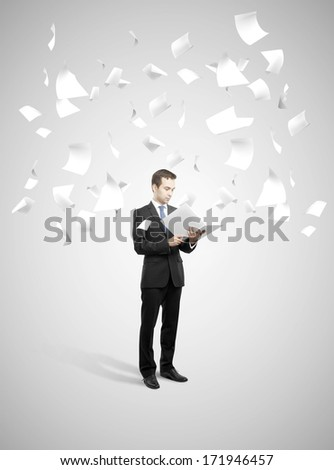 businessman holding book with flying around papers - stock photo