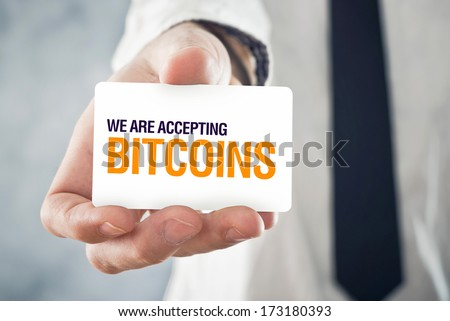 Businessman holding card with title WE ARE ACCEPTING BITCOINS. Selective focus on card and fingers. - stock photo