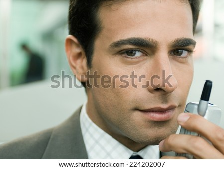 Businessman holding cell phone near face - stock photo