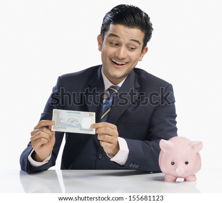 Businessman holding currency note and looking at piggy bank - stock photo