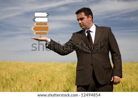 businessman holding direction sign in the hand outdoor - focus on the sign - stock photo