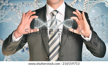 Businessman holding dna spiral in hands - stock photo