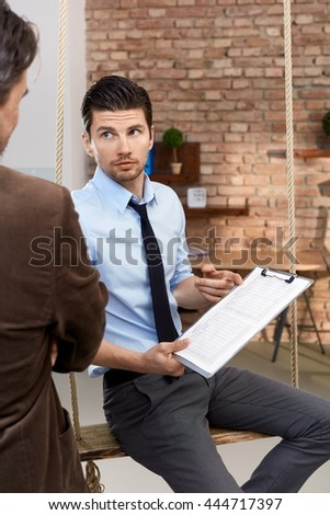 Businessman holding document, showing it to colleague, sitting in swing in modern office. - stock photo