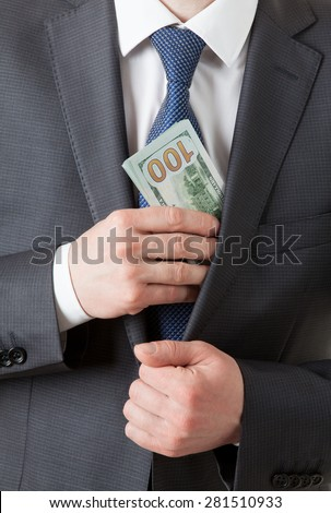 Businessman holding dollars/putting dollars in a pocket, closeup shot - stock photo