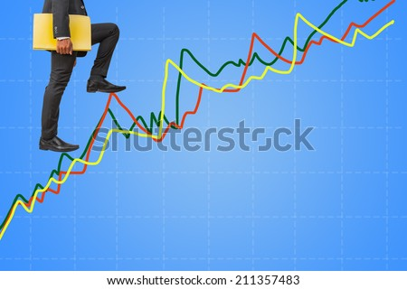 businessman holding files climbing on line graph to success - stock photo
