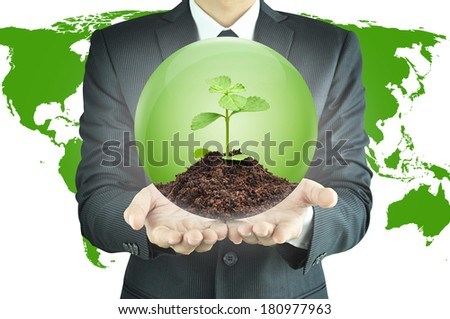 Businessman holding green sapling with soil inside the sphere - conservation concept - stock photo