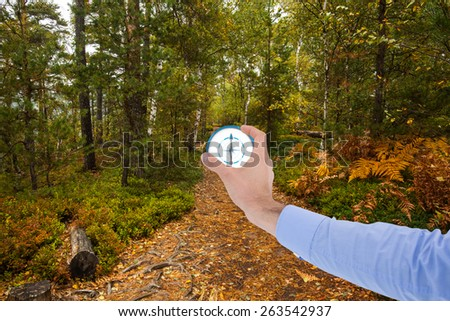 Businessman holding hand out in presentation against scenic view of walkway along lush forest - stock photo