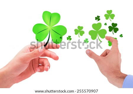 Businessman holding hand out in presentation against shamrock - stock photo