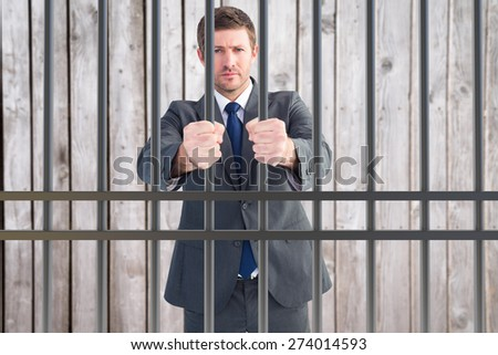Businessman holding his hands out against digitally generated grey wooden planks - stock photo