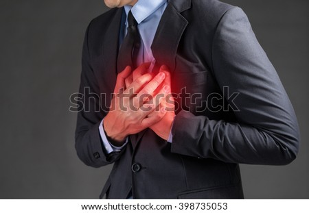 Businessman holding his heart in pain - stock photo