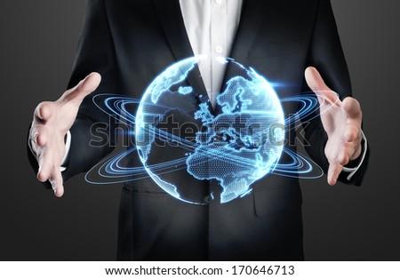 Businessman holding holographic globe - stock photo