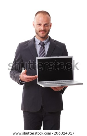 Businessman holding laptop with blank screen, smiling. - stock photo