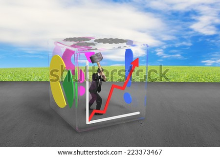 businessman holding large hammer to break glass cube on  concrete floor with nature sky meadow background - stock photo