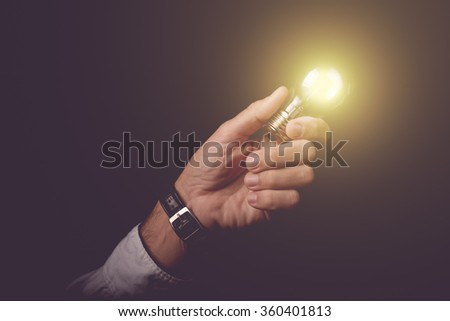 Businessman holding light bulb, concept of new ideas, business innovation and creativity, retro toned image, selective focus. - stock photo