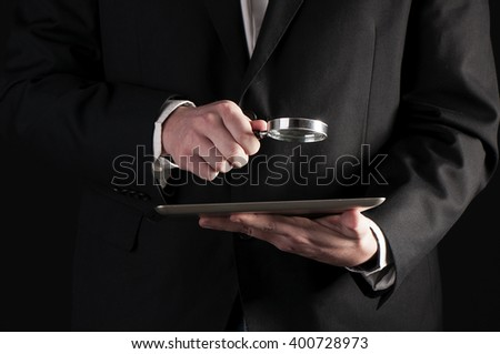 Businessman holding magnifying glass and digital tablet. Searching and examining concept - stock photo