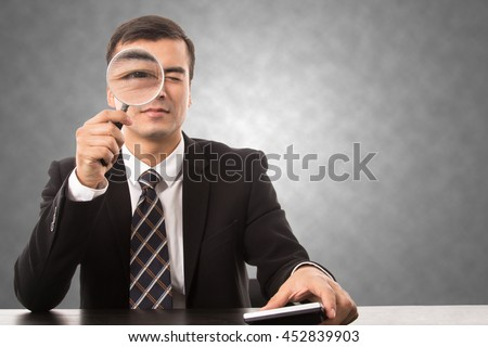 Businessman holding magnifying glass for search data and information. - stock photo