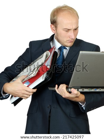 businessman holding many of things like briefcase, newspapers sheet of papers and laptop - stock photo