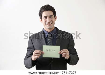 Businessman holding message card, portrait - stock photo