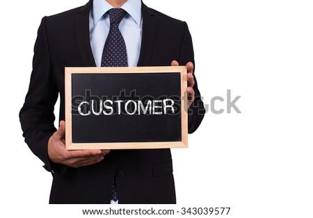 Businessman holding mini blackboard with CUSTOMER message - stock photo