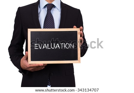 Businessman holding mini blackboard with EVALUATION message - stock photo