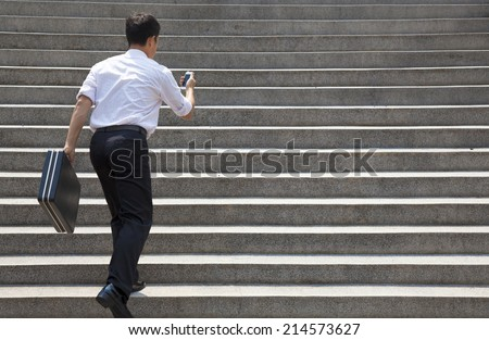 businessman holding mobile and in hurry to run up on stairs - stock photo