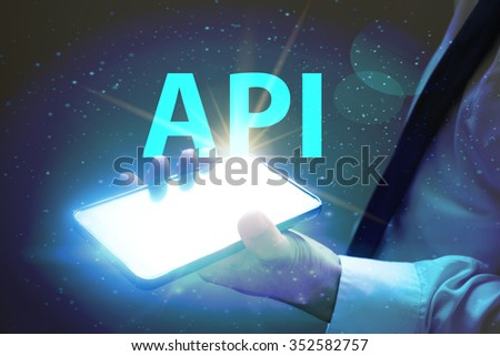 businessman holding mobile phone with API text on virtual screen. Internet concept.  - stock photo