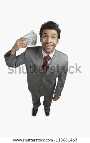 Businessman holding money and smiling - stock photo