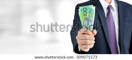 Businessman holding money, Australian dollar (AUD) banknotes, in his fist - business and financial panoramic header background - stock photo