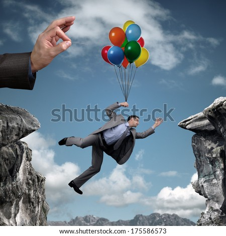 Businessman holding on to balloons above a cliff trying to escape hand bursting his balloon and bridge the gap concept for business adversity, risk, challenge or bullying - stock photo