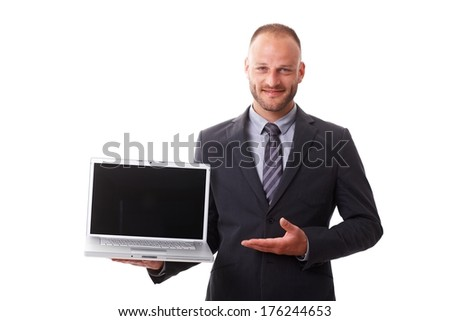 Businessman holding open laptop with blank screen, smiling, showing laptop with other hand. - stock photo