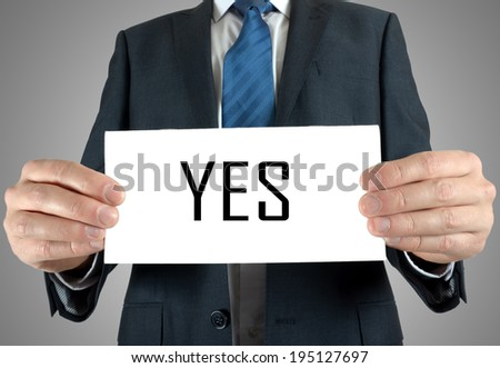 Businessman holding or showing card with Yes word - stock photo