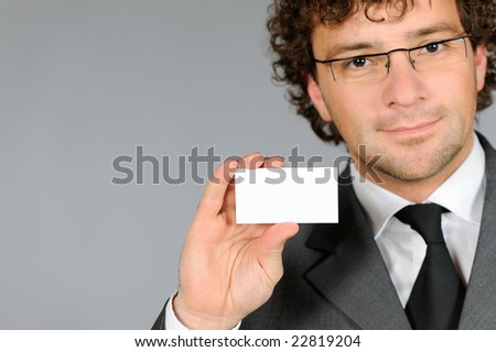Businessman holding out a blank business card - stock photo
