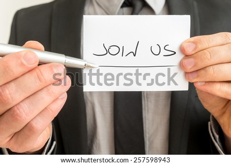 Businessman holding out a pen and card with the handwritten message - Join Us - in a conceptual image, close up view of the card. - stock photo